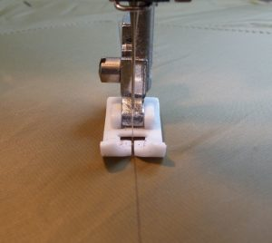 Close-up of white presser foot used to sew khaki fabric