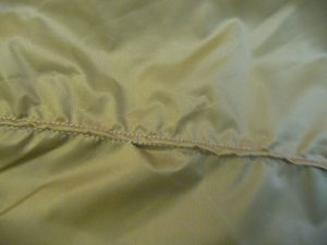 Close-up of wrinkled & puckered seam in khaki fabric
