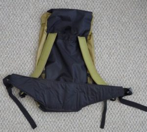 Front view of a black and khaki backpack on a grey background