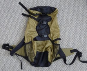 Rear view of a black and khaki backpack on a grey background