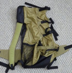 Side view of a black and khaki backpack on a grey background