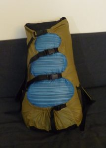 Side View of Khaki Rezac Pack with blue drybag on a grey background