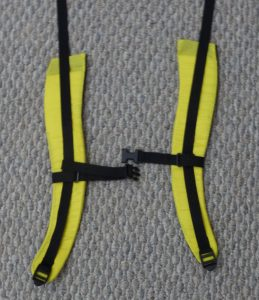 Yellow and black backpack shoulder straps on a grey background