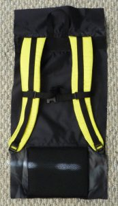 Black and yellow backpack back on a grey background