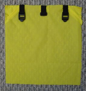 Yellow square top back panel wtih black webbing and hardware on a grey background