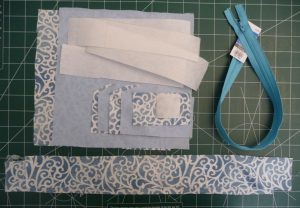 Pale blue interior fabric, blue & white exterior fabric, white stabilier and blue zipper all on a green background