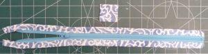 Swirled blue & white zipper tab (top) and zipper panel (bottom) on a green background