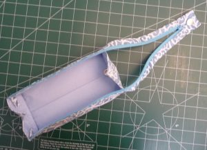 Open Zola Pen Case with pale blue interio and blue & white swirled exteior on a green background