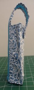 Side view Zola Pen Case made with blue and white wirling fabric & a round silver snap