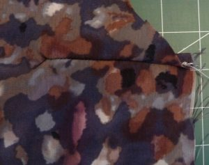 Close-up of dart sewn in multicolored fabric on a green background