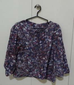 Multicoloured blouse hanging on a black hanger (cream colored background)