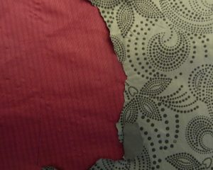 Interior closeup of pink raincoat with peeling grey waterproofing