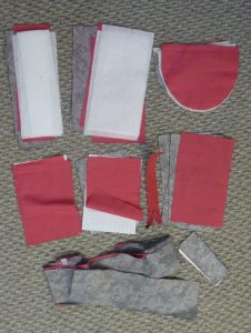 Pink, white and grey pieces for a purse on a grey background