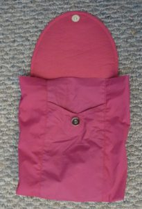 Pink bag exterior with the flap open on a grey background
