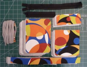 Zipers (black), exterior fabric (multicolored) bias tape (grey) and fusible interfacing and fusible fleece (white)