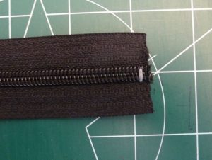 Closeup of black zipper tape with white stitches at cut end