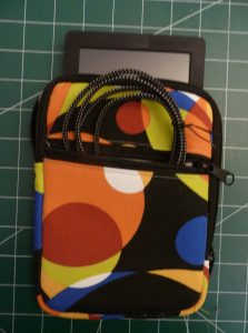 E-reader and chargning cable sticking ouf the pockets of a multicolored Zippered E-reader Case