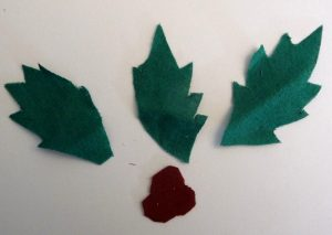 Close-up of 3 green fabric leaves and 3 red fabric berries on a white background